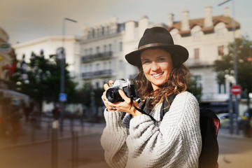Good looking brunette photographer with vintage camera in city