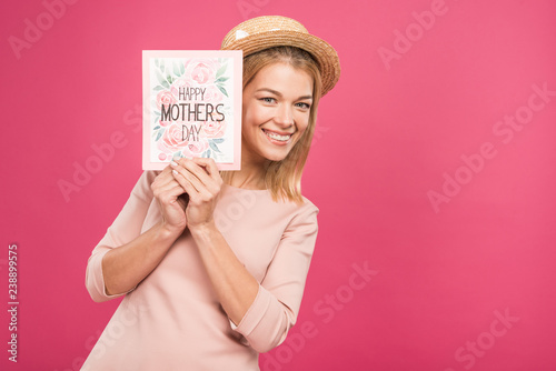 """smiling woman holding """"happy mothers day"""" greeting card, isolated on pink"""