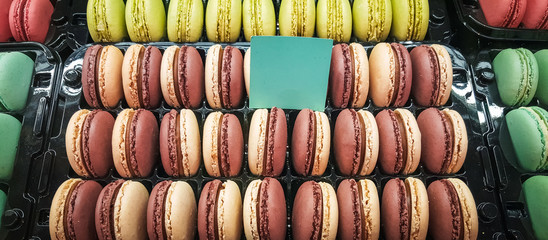 Assortment of macarons in a plastic container on sale in a patisserie