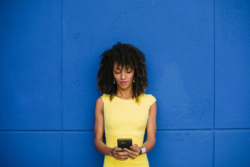 Portrait of fashionable businesswoman in yellow dress text messaging against blue background