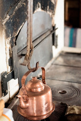 Copper kettle hanging on hook above hearth