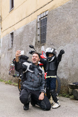 Happy father and son taking a selfie on a motorbike trip