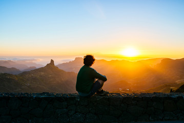 Spain, Canary Islands, Gran Canaria, back view of man sitting on a wall watching sunset over mountainscape