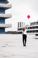 Back view of young woman with red balloon