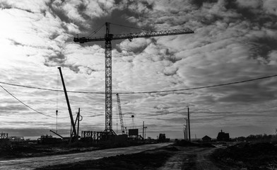 View of the construction site with cranes and high-rise residential buildings. Black and white photo