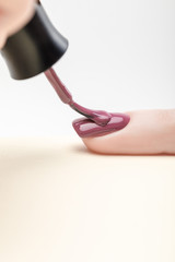 manicurist applying purple nail polish on fingernail of woman on grey background