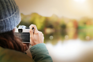 Close up of woman taking photos outdoors in fall