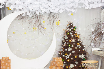 Location for a photo shoot. Attributes of the New Year. Decorated Christmas tree. Moon with stars. Festive lighting.