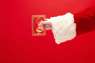 Santa holding an old sand clock on red background. The season, winter, holiday, celebration, gift concept