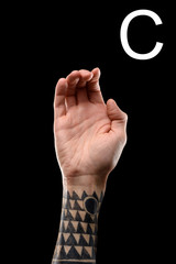 tattooed hand showing latin letter - C, sign language, isolated on black
