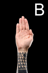 sign language with tattooed male hand and cyrillic letter, isolated on black