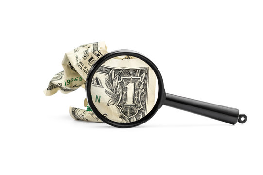 Crumpled one dollar bill with magnifying glass on white.