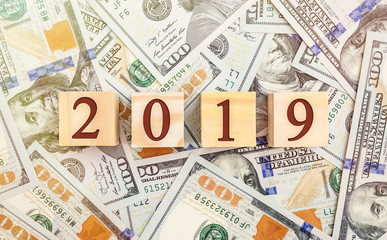 Wooden cubes with numbers 2019 on background of dollar bills. Top view.