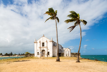 Church and fortress of San Antonio on Mozambique island, with two palm trees on sand. Indian ocean coast, Nampula province, Mozambique. Fortim de Santo António na Ilha de Moçambique.