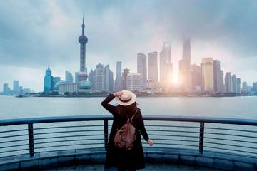 Woman tourist is enjoy watching landmark view city skyline business district in Shanghai, China.