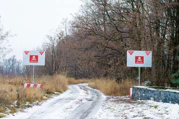 mined dirt road, warning signs danger mines