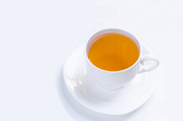 Orange herbal flavored christmas tea with cinnamon and cardamom honey white cup on a white wooden table