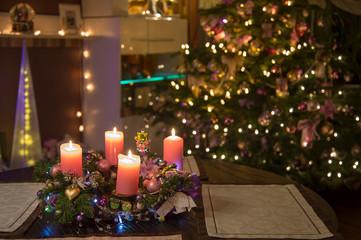Die vier Kerzen am Adventskranz sind angezündet. Im Hintergrund leuchtet der Weihnachtsbaum. Das Bild hat viel Bokeh durch viele Lichter.