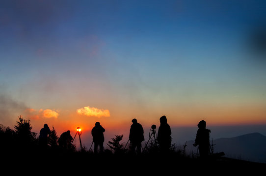 Photographers silhouetted against misty sunset on top of Mt. Mitchell in Appalachian Mountains in western North Carolina.