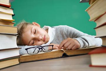 Tired schoolgirl sleeping on book. Photo of little girl in school around books. Education concept