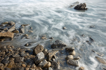 Blurred waves crashing on the stones of the beach