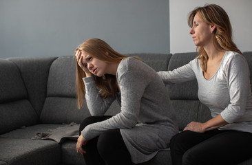 Depressed teen suffering from anxiety being taken care of by her caring mother