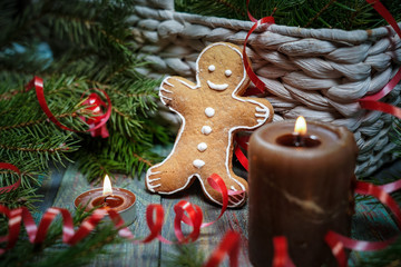 A gingerbread man with Christmas decorations and lots of fir branches.