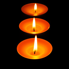 Drei brennende Teelichter vor schwarzem Hintergrund