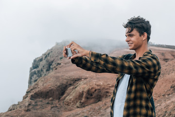 Young handsome guy making landscape photo on mobile phone, while standing on the mountain hill.