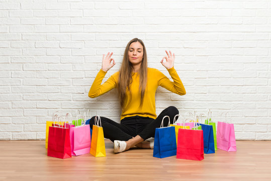 Young girl with lot of shopping bags in zen pose