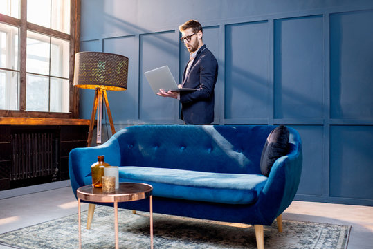 Portrait of an elegant businessman sitting with laptop on the couch at the luxury blue office interior