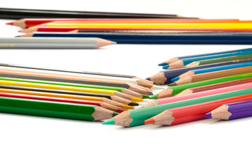 Color pencils pink light blue green yellow and red on white background.