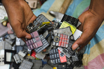 Desire Koffi, 24-year-old artist, holds discarded phone keyboards at his workshop in Abidjan