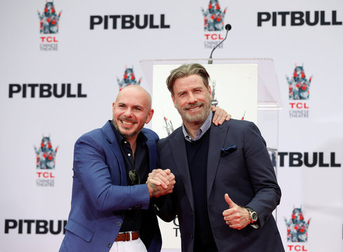 American rapper Pitbull poses with actor John Travolta during a ceremony of placing his hands and footprints in cement in the forecourt of the TCL Chinese theatre in Los Angeles