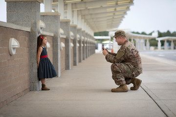 Soldier taking a picture of his daughter