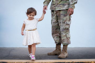 Soldier holding his daughter's hand