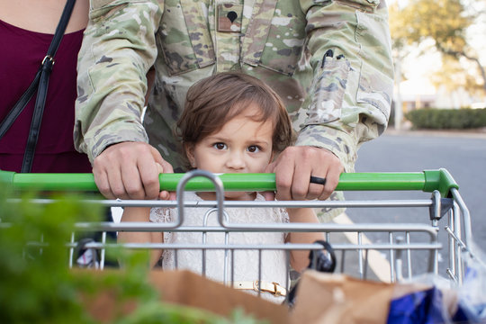Toddler pushing a shopping cart with her