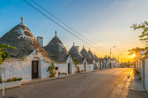 Wall mural Trulli houses in Alberobello city at sunset time,  Apulia, Italy