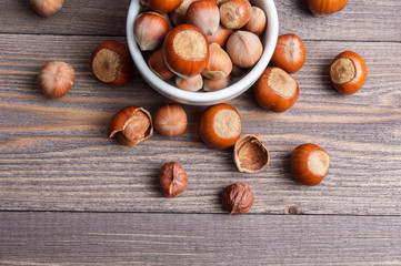 Filbert nuts in white porcelain bowl on wooden background