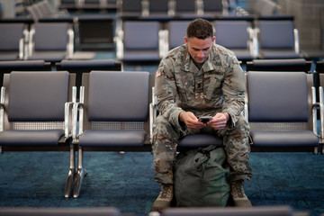 Soldier looking at his cell phone while waiting at an airport