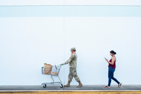 Soldier pushing a shopping cart holding girl with wife behind him