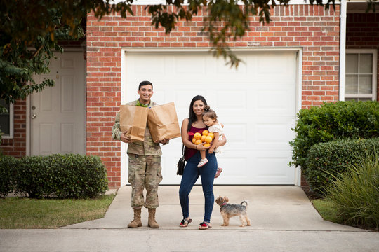 Soldier and wife holding groceries and daughter