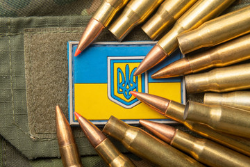 Ukrainian flag and coat of arms against camouflage and battle bullets. The concept of the Ukrainian defense army, highlight