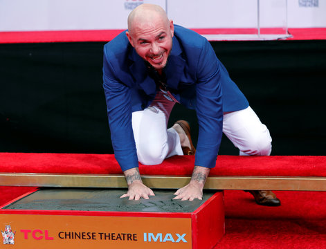 American rapper Pitbull places his hands in cement during a ceremony in the forecourt of the TCL Chinese theatre in Los Angeles