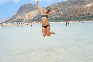 Happy smiling young woman is jumping on the beach. Concept of friendly family. Happy summer days. Balos Lagoon. Elafonisi Beach - Crete, Greece. - Image