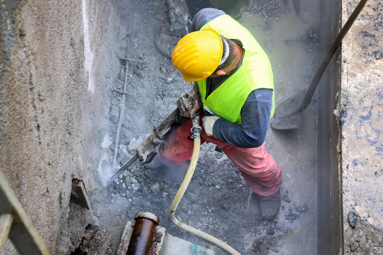 Worker demolish old concrete wall with jackhammer