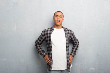 Young african american man with checkered shirt suffering from backache for having made an effort