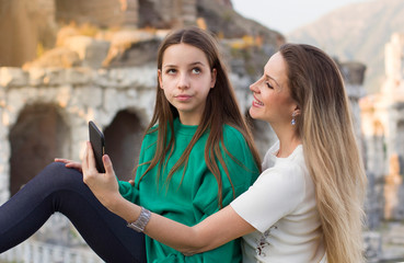 Mother and daughter teenager taking selfie portrait on smartphone in city