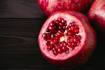 Fruits of pomegranate with cutted top on the dark wooden background
