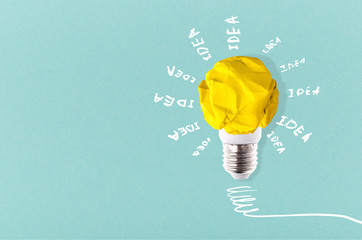Wall Mural - crumpled yellow paper lightbulb with inscription idea around on a blue background